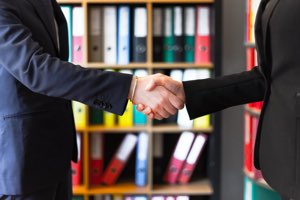 Business research - two people shaking hands